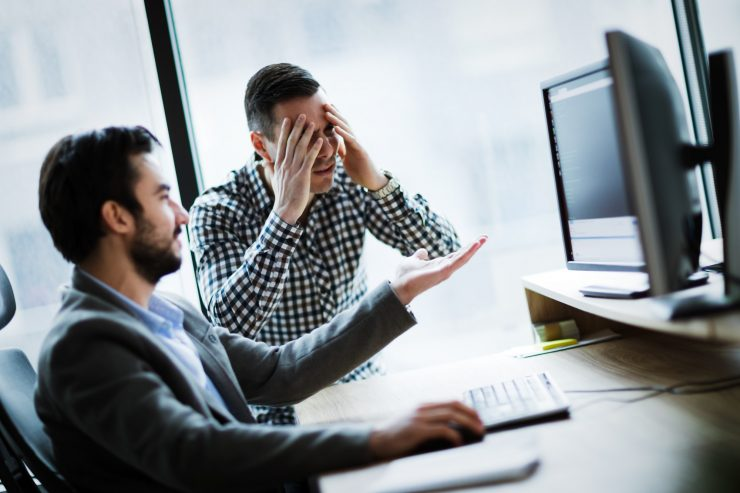 Business colleagues working on computer and having problems - the effect of lack of professional outsourced IT services