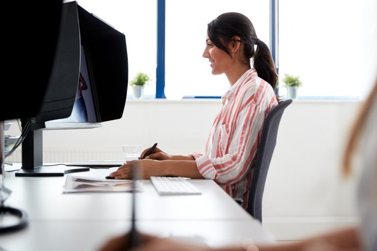 Female Retoucher Working At Computer Using Graphics Tablet In Post Production Company